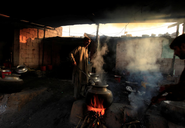 A man cooks rice to be donated by devotees at the shrine of Bari Imam in Islamabad, Pakistan December 2, 2016. (Photo by Faisal Mahmood/Reuters)