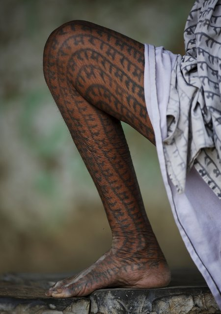 Punai Bai, 75, a follower of Ramnami Samaj, who has tattooed the name of the Hindu god Ram on her full body, poses for a picture outside her house in the village of Gorba, in the eastern state of Chhattisgarh, India, November 15, 2015. (Photo by Adnan Abidi/Reuters)