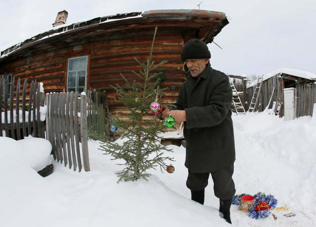 Mikhail Baburin, 66, decorates a fir tree for New Year and Christmas celebrations in front of his house in the remote Siberian village of Mikhailovka, Krasnoyarsk region, Russia, December 5, 2016. (Photo by Ilya Naymushin/Reuters)