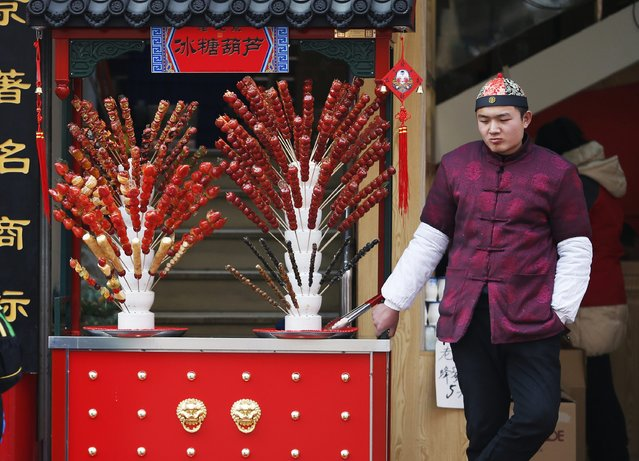 A vendor selling traditional candies waits for customers at a shopping district in Beijing February 10, 2015. (Photo by Kim Kyung-Hoon/Reuters)