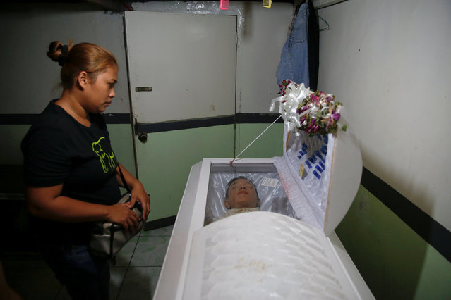Rita, the wife of Florjohn Cruz, looks at his body inside a coffin after his autopsy at Eusebio Funeral Service in Manila, Philippines October 28, 2016. (Photo by Damir Sagolj/Reuters)