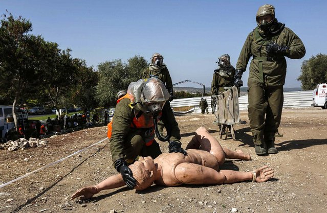 An Israeli soldier from the home front command wearing protective gear kneels next to a dummy during a drill simulating a chemical attack in the town of Beit Shemesh, near Jerusalem, on October 2, 2013. (Photo by Baz Ratner/Reuters)