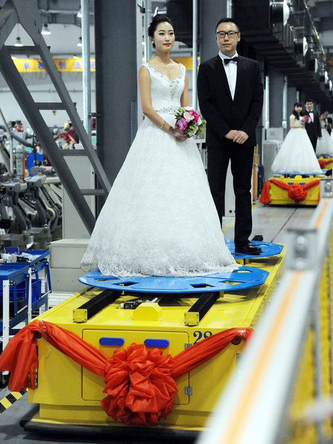 Couples stand on the robot moving forward during a group wedding ceremony at a robot factory on January 20, 2016 in Shenyang, Liaoning Province of China. Various types of robot served a five-couple group wedding at a robot factory on Wednesday in Shenyang.  (Photo by ChinaFotoPress/ChinaFotoPress via Getty Images)