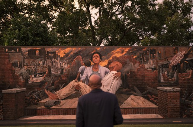 In this Thursday, May 27, 2021 file photo, Darius Kirk looks at a mural depicting the Tulsa Race Massacre in the historic Greenwood neighborhood ahead of centennial commemorations of the massacre in Tulsa, Okla. The horror and violence visited upon Tulsa's Black community in 1921 didn't become part of the American story. Instead, it was pushed down, unremembered and untaught until efforts decades later started bringing it into the light. (Photo by John Locher/AP Photo/File)