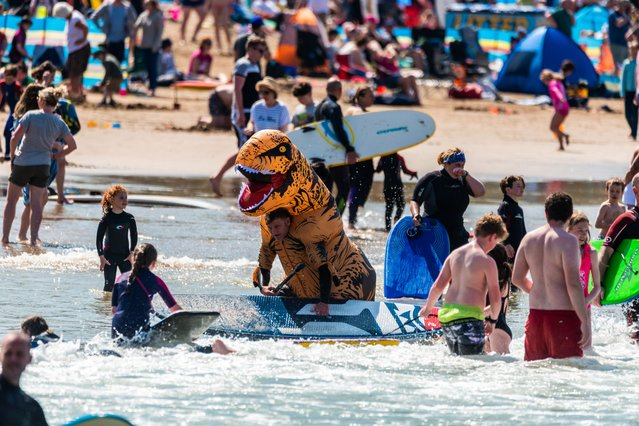 Prankster John Hiscock donned the inflatable costume and went paddle boarding to the delight of crowds at Woolacombe Beach, Devon, a county in southwest England on June 2, 2021. By the way, dino experts think T-Rex struggled to swim due to its short arms but did paddle across rivers. (Photo by South West News Service)