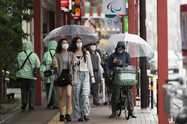 People wearing face masks to help curb the spread of the coronavirus walk around in the famed Asakusa shopping area on a rainy day in Tokyo on Thursday, May 27, 2021. (Photo by Hiro Komae/AP Photo)
