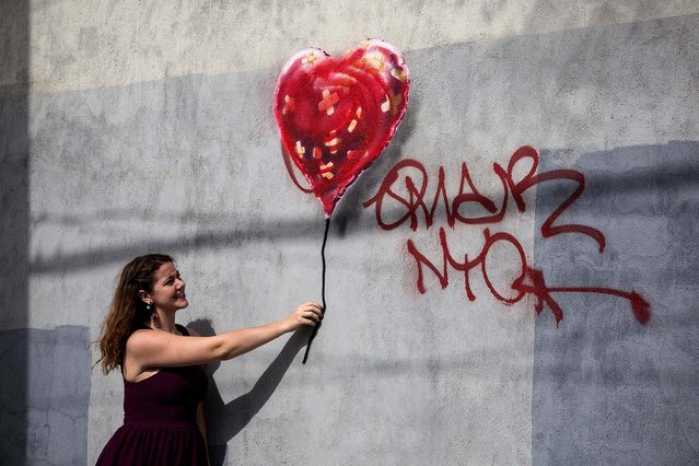 A woman poses with a Banksy piece depicting a heart-shaped balloon covered in bandages, on October 7 in the Red Hook neighborhood of the Brooklyn borough of  New York City. The piece was defaced with red spray paint shortly after being completed. (Photo by Andrew Burton/Getty Images)