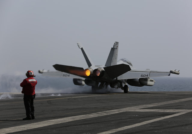 A U.S. military plane takes off from the flight deck of the USS Carl Vinson aircraft carrier in the Persian Gulf, Thursday, March 19, 2015. (Photo by Hasan Jamali/AP Photo)
