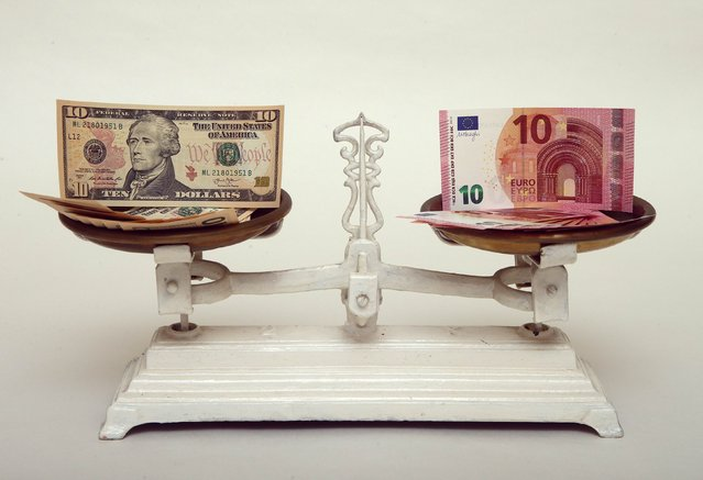 U.S. Dollar and Euro banknotes on a pair of scales in Vienna are seen in this March 11, 2015 file photo. The euro's slide toward parity with the dollar will provide a much-needed boost for European companies this year and force U.S. rivals to adapt their businesses or risk losing market share. (Photo by Heinz-Peter Bader/Reuters)