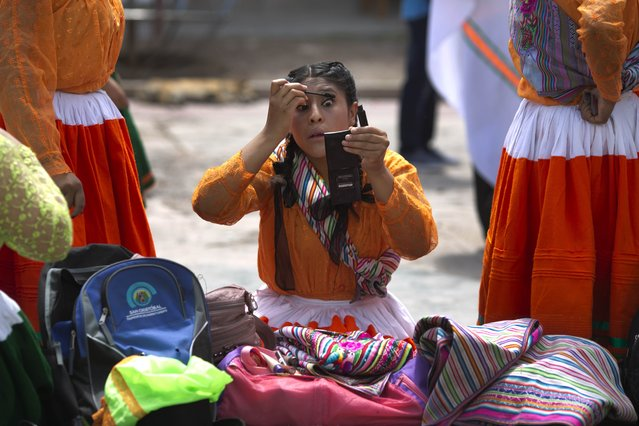 An Andean woman in traditional dress, applies mascara before the carnival in Ayacucho, Peru, Thursday, January 28, 2016. The carnival in the Andean region of Peru begins at the same the time  farmers plant their crops. (Photo by Martin Mejia/AP Photo)