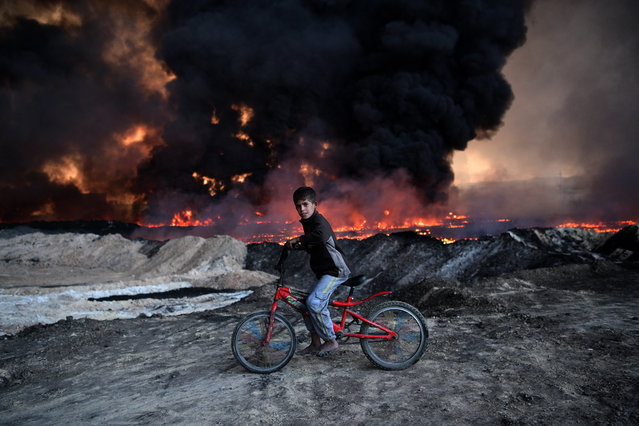 A boy pauses on his bike as he passes an oil field that was set on fire by retreating ISIS fighters ahead of the Mosul offensive, on October 21, 2016 in Qayyarah, Iraq. Several hundred Iraqi families have been made to leave their homes for Mosul by Islamic State fighters as the UN warns they could be used as human shields. ISIS have attacked Kirkuk today as Kurdish and Iraqi forces, backed by a coalition including Britain and the U.S.A continue their offensive to retake Iraq's second largest city of Mosul. (Photo by Carl Court/Getty Images)