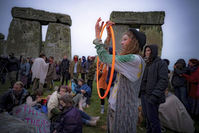 People inside the stone circle during Summer Solstice at Stonehenge, where some people jumped over the fence to enter the stone-circle to watch the sun rise at dawn of the longest day of the year in the UK, in Amesbury, England, Monday June 21, 2021. The prehistoric monument of ancient stones have been officially closed for the celebrations due to the coronavirus lockdown, but groups of people ignored the lockdown to mark the Solstice, watched by low key security. (Photo by Ben Birchall/PA Wire via AP Photo)