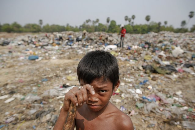 Seu, a 13-year-old boy who makes 25 US cents per day, pauses from working at landfill dumpsite outside Siem Reap March 19, 2015. (Photo by Athit Perawongmetha/Reuters)