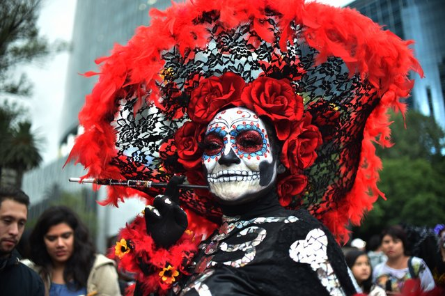 """People fancy dressed as """"Catrina"""" take part in the """"Catrinas Parade"""" along Reforma Avenue, in Mexico City on October 21, 2018. Mexicans get ready to celebrate the Day of the Dead highlighting the character of La Catrina which was created by cartoonist Jose Guadalupe Posada, famous for his drawings of typical local, folkloric scenes, socio-political criticism and for his illustrations of """"skeletons"""" or skulls, including La Catrina. (Photo by Rodrigo Arangua/AFP Photo)"""