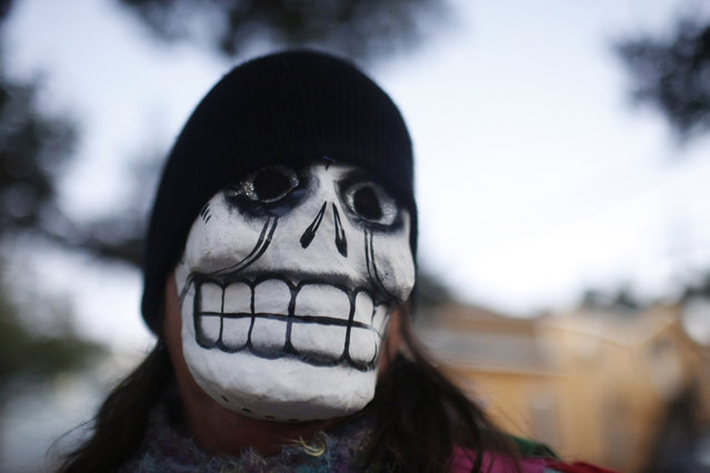 A parade-goer walks the streets with the North Side Skull & Bone Gang, during the wake up call for Mardi Gras, Tuesday, February 9, 2016, in New Orleans. (Photo by Brynn Anderson/AP Photo)