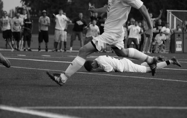 """""""Pain"""". A player on Pacific Lutheran University's soccer team clinches his face in agony after a hard hit with a player from the opposing team. Taken September 25, 2012. Photo location: Parkland, Washington, United States. (Photo and caption by Thomas Soerenes/National Geographic Photo Contest)"""