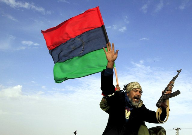 A rebel soldier gestures atop a car as he heads to Brega, in Ajdabiya March 2, 2011. (Photo by Goran Tomasevic/Reuters)