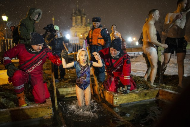 Russian Emergency Situations employees help a girl to bath in the icy water on Epiphany at the Church of the Holy Trinity in Ostankino near TV Tower in Moscow, Russia, Friday, January 18, 2019. Across Russia, the devout and the daring are observing the Orthodox Christian feast day of Epiphany by immersing themselves in frigid water through holes cut through the ice of lakes and rivers. Epiphany celebrates the revelation of Jesus Christ as the incarnation of God through his baptism in the River Jordan. (Photo by Alexander Zemlianichenko/AP Photo)