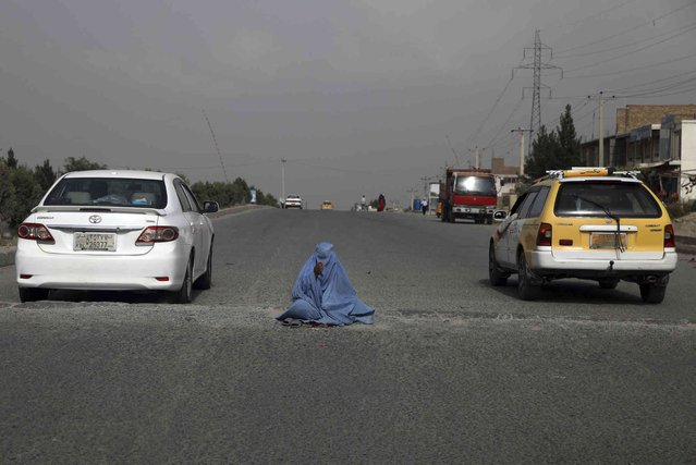 A woman asks for donations from drivers on a street on the outskirts of Kabul, Afghanistan, Saturday, July 31, 2021. (Photo by Rahmat Gul/AP Photo)
