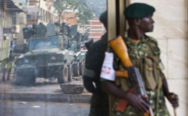 A convoy of armored personnel carriers is seen reflected in a shop window as a Ugandan soldier stands guard on a street corner, shortly after the election result was announced, in downtown Kampala, Uganda, Saturday, February 20, 2016. (Photo by Ben Curtis/AP Photo)