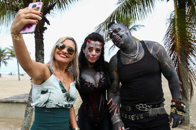 Brazilian tattoo artist Michel Praddo, also known as Diabao or Human Satan, and his wife Carol Praddo, known as Mulher Demonia or Demon Woman, take a picture with a fan at the beach shore in Praia Grande, Brazil on August 18, 2021. Despite his frightening image, Prado says he has a good heart. His wife Carol Prado, 36, who is known as Demon Woman, also altered her body to fit the image. The Sao Paulo-based couple have undergone their most extreme modifications during the last five years. (Photo by Carla Carniel/Reuters)