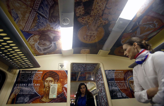 A train hostess stands in a train carriage decorated with the iconic figures as it departs from Belgrade to Mitrovica, Kosovo at Belgrade's railway station, Serbia, Saturday, January 14, 2017. (Photo by Darko Vojinovic/AP Photo)