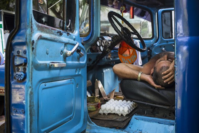 In this July 21, 2018 file photo, a driver takes a nap in the cabin of his truck at an outdoor food market in Havana, Cuba. (Photo by Desmond Boylan/AP Photo)