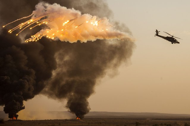 An Israeli AH-64 Apache longbow helicopter launches anti-missile flares during an air show at the graduation ceremony of Israeli air force pilots at the Hatzerim base in the Negev desert, near the southern Israeli city of Beersheva on December 26, 2013. (Photo by Jack Guez/AFP Photo)
