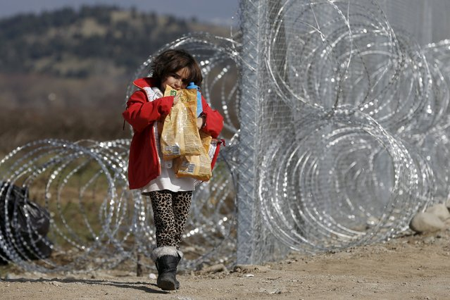 A migrant child from Afghanistan carries food next to a border fence at the Macedonian-Greek border in Gevgelija, Macedonia February 23, 2016. (Photo by Marko Djurica/Reuters)