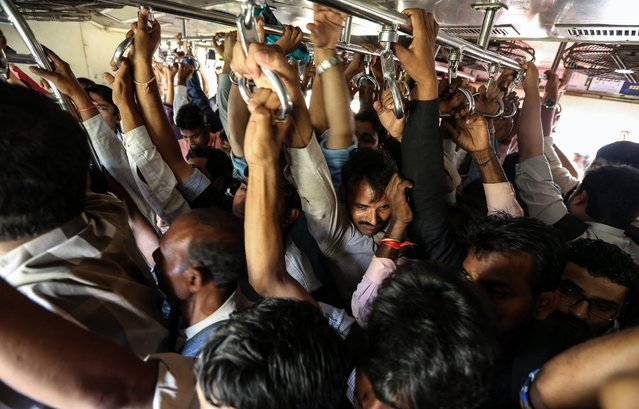 Commuters travel on a local train in Mumbai, India, 24 February 2016. The Indian Union Minister of Railway, Suresh Prabhu, is set to present the rail budget for the year 2015-16, to the Indian Parliament on 25 February 2016. (Photo by Divyakant Solanki/EPA)
