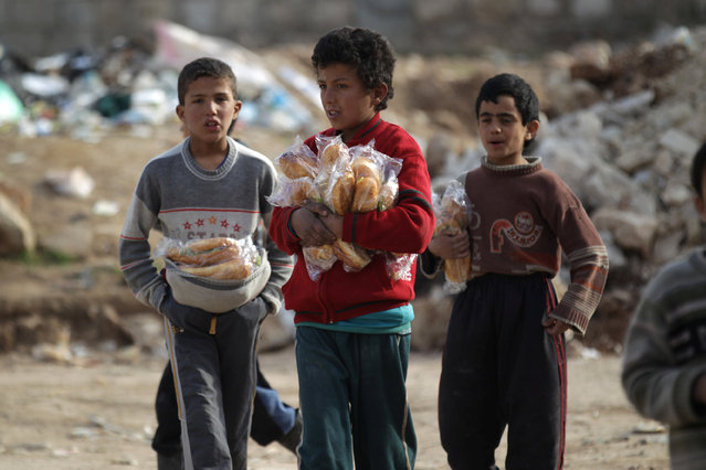 Boys carry sandwiches near rubble of damaged buildings in al-Rai town, northern Aleppo countryside, Syria January 20, 2017. (Photo by Khalil Ashawi/Reuters)