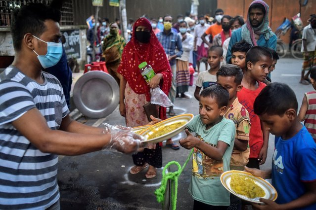 This picture taken on July 26, 2021 shows volunteer from Mehmankhana, a non-profit organization, distributing food for pandemic affected people during a lockdown to contain the spread of the Covid-19 coronavirus, at Lalmatia area. (Photo by Munir Uz Zaman/AFP Photo)