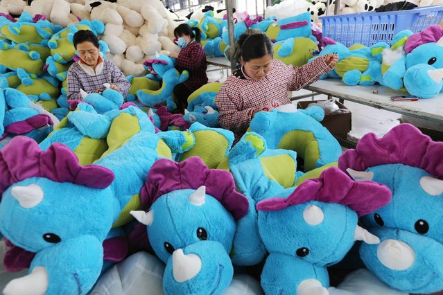 This picture taken on April 14, 2015 shows workers producing dolls in a factory in Lianyungang, east China's Jiangsu province. China's economy expanded 7.0 percent year-on-year in the first quarter, official data showed April 15, slumping to a new post global financial crisis low and raising analyst expectations for more action to bolster growth in the world's second-largest economy. (Photo by AFP Photo)