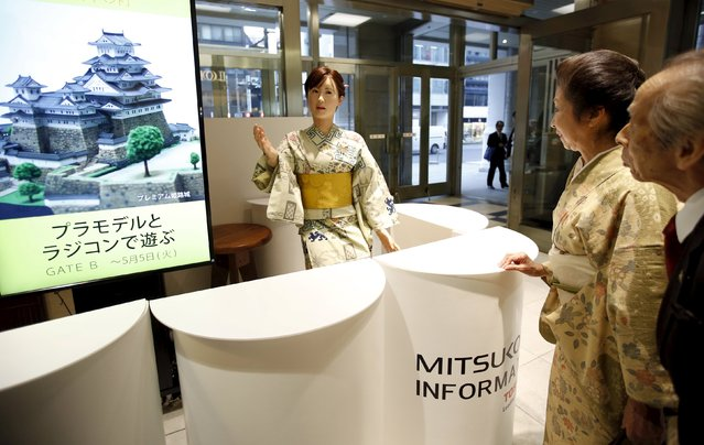 Visitors look at a kimono-clad android robot (C) named Aiko Chihira, developed by Toshiba Corp., at the reception desk of Nihonbashi Mitsukoshi department store in Tokyo April 20, 2015. (Photo by Issei Kato/Reuters)