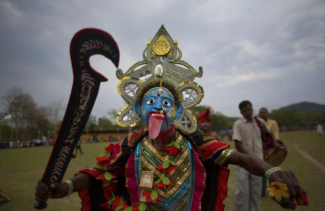 A man dressed as Hindu goddess Kali dances during the Suwori festival in Boko about 75 kilometers (47 miles) west of Gauhati, India, Monday, April 20, 2015. Traditional elephant fights, elephant races, tug of war and dances mark this festival which coincides with the Assamese Rongali Bihu, or the harvest festival of the northeastern Indian state of Assam. (Photo by Anupam Nath/AP Photo)