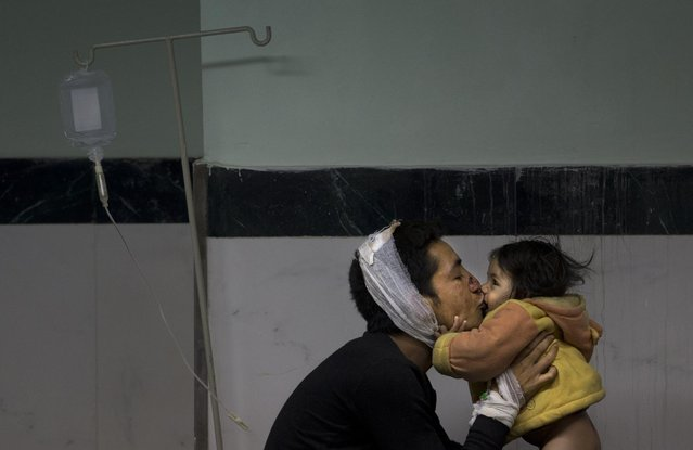 Earthquake injured Nepalese man Suresh Parihar plays with his daughter Sandhya at a hospital, in Kathmandu, Nepal, Sunday, April 26, 2015. (Photo by Manish Swarup/AP Photo)