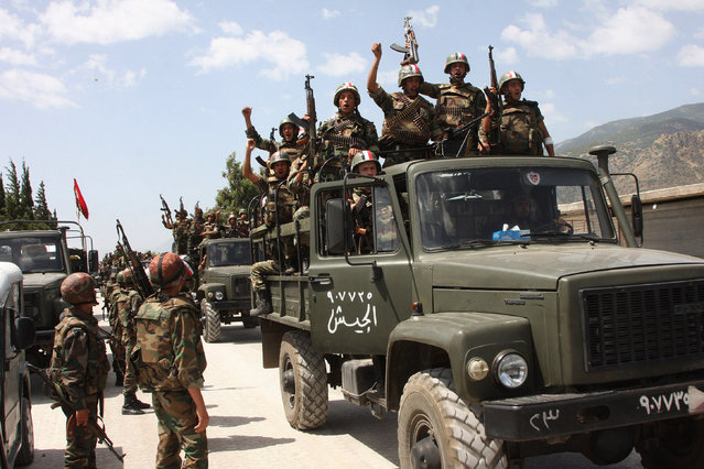 In this file photo taken on Friday, June 10, 2011, during a government organized tour for the media, shows Syrian army soldiers standing on their military trucks chanting slogans in support of Syrian President Bashar Assad, as they enter a village near the town of Jisr al-Shughour, north of Damascus, Syria. (Photo by AP Photo)