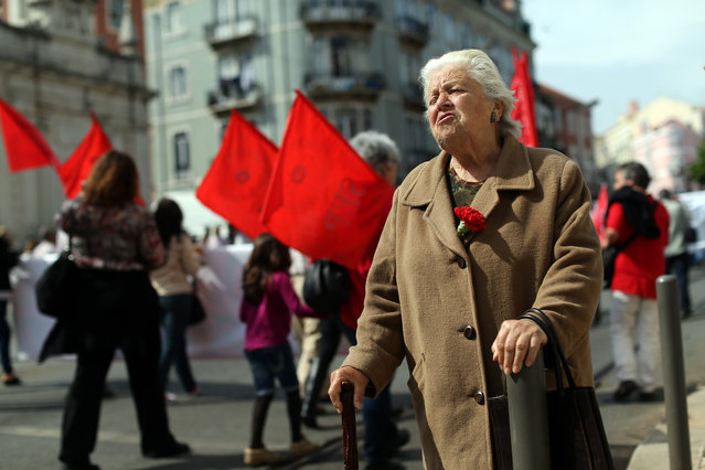 Portuguese Maria da Luz, 88, wearing a red carnation on her coat, shouts slogans during a march marking the international May Day, in Lisbon, Friday, May 1, 2015. A red carnation is the symbol of the revolution that restored the democracy in Portugal in 1974. (Photo by Francisco Seco/AP Photo)