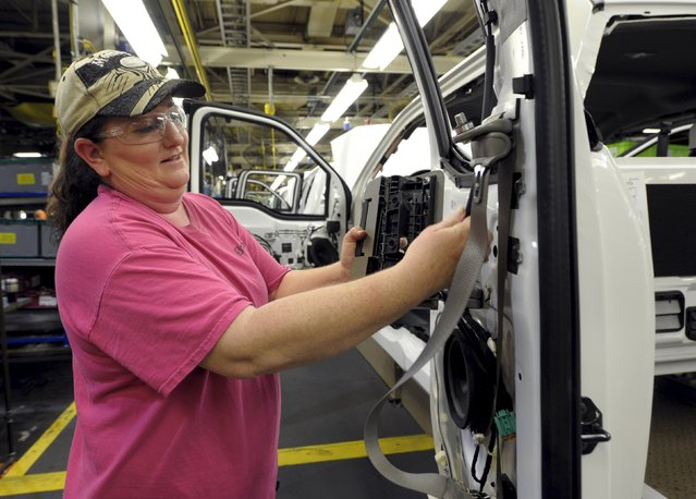 Auto worker Melinda Barnett installs components into a F150 at Ford's Kansas City Assembly Plant where new aluminum intensive Ford F-Series pickup is built in Claycomo, Missouri May 5, 2015. (Photo by Dave Kaup/Reuters)