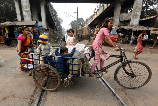 A girl transports drinking water containers on a tricycle as a woman helps her, after filling them from a roadside municipal water tap in Kolkata, India, February 2, 2017. (Photo by Rupak De Chowdhuri/Reuters)