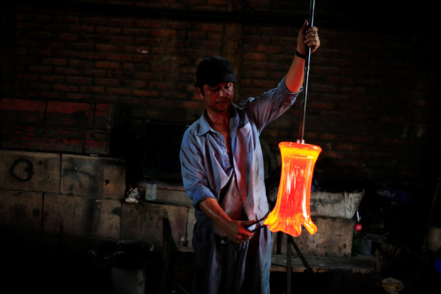 A glassmaker forms molten glass next to a furnace at Cespedes factory in Olocuilta, El Salvador February 8, 2017. (Photo by Jose Cabezas/Reuters)