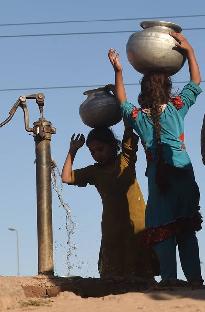 Pakistani girls fill water pots from a hand pump at a slum area of Lahore on March 21, 2016, on the eve of World Water Day. International World Water Day is held annually on March 22 to focus global attention on the importance of water and advocating for the sustainable management of our water resources. (Photo by Arif Ali/AFP Photo)