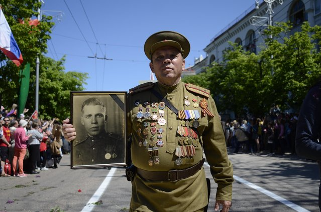 A participant in a march honoring Soviet soldiers of WWII carries a portrait after a military parade marking the 70th anniversary of the victory over Nazi Germany in WWII in Sevastopol, Crimea, Saturday, May 9, 2015. (Photo by Anton Volk/AP Photo)