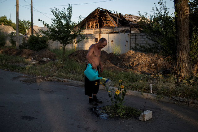 Man watering flowers on a street in the destroyed village of Spartak. Ordinary people became victims of the conflict between self-proclaimed republics and the official Ukrainian authorities from 2014 onwards in the region of Donbass. Disaster came into their lives unexpectedly. These people were involved in the military confrontation against their will. They experienced the most terrible things: the death of their friends and relatives, destroyed homes and the ruined lives of thousands of people. (Photo by Valery Melnikov/Reuters/Rossiya Segodnya/Courtesy of World Press Photo Foundation)