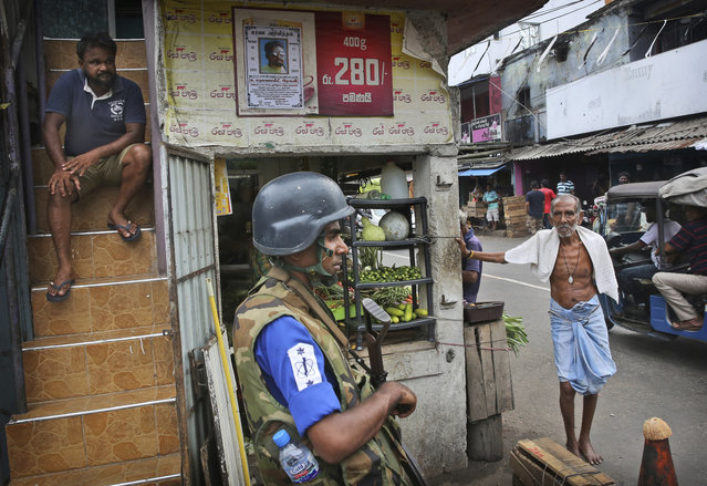 Sri Lankans stand near a roadside shop as a Naval soldier stand near damaged St. Anthony's Church, in Colombo, Saturday, April 27, 2019. Sri Lankan security forces have found 15 bodies, including six children, after militants linked to the Easter bombings set off explosives during a raid on a house in the country's east. (Photo by Manish Swarup/AP Photo)