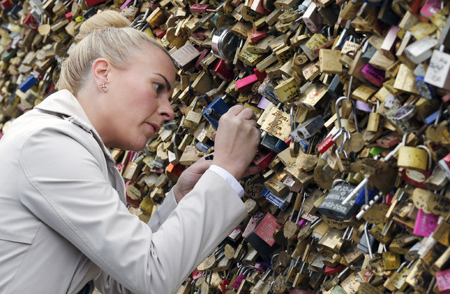 """A tourist hangs a padlock of love on the """"Pont Neuf"""" during Valentine's Day on February 14, 2017 in Paris, France. Valentine's Day is the day of love in the world.The Paris City Hall will shortly be organizing an auction of love locks from the """"Pont des arts"""" with profits going to help refugees. (Photo by Chesnot/Getty Images)"""