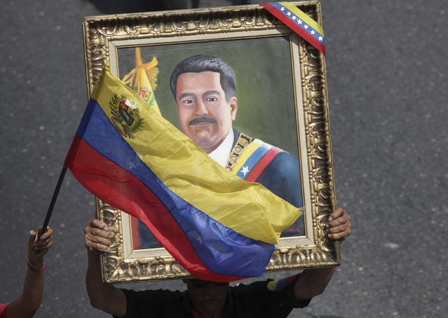 Supporters of Venezuelan President Nicolas Maduro carry a portrait of him during a rally in Caracas, Venezuela, Wednesday, May 1, 2019. (Photo by Boris Vergara/AP Photo)