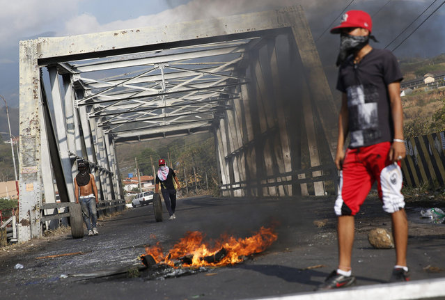 Demonstrators roll tires to build a barricade and block a bridge during protests against Nicolas Maduro's government in San Cristobal, about 410 miles (660 km) southwest of Caracas, February 26, 2014. Pope Francis called on Wednesday for an end to violence in Venezuela that has killed at least 13 people and urged politicians to take the lead in calming the nation's worst unrest for a decade. (Photo by Carlos Garcia Rawlins/Reuters)