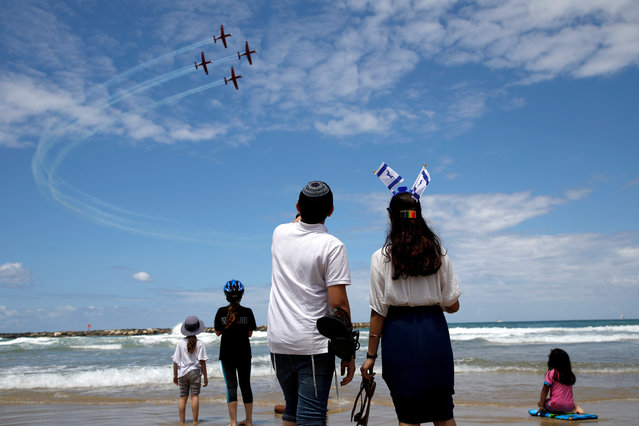 People watch as Israeli Air Force planes fly in formation over the Mediterranean Sea during an aerial show as part of the celebrations for Israel's Independence Day marking the 71st anniversary of the creation of the state, in Tel Aviv, Israel on May 9, 2019. (Photo by Corinna Kern/Reuters)