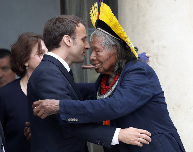 Kayapo tribal leader Raoni Metuktire, right, hugs French President Emmanuel Macron, after a meeting at the Elysee Palace, in Paris, Thursday, May 16, 2019. (Photo by Christophe Ena/AP Photo)